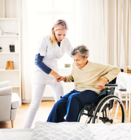 caregiver assisting senior woman to stand up in the wheelchair