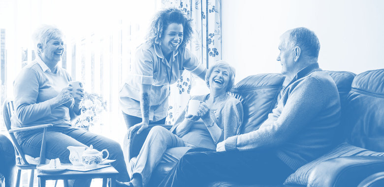 a group of seniors and caregiver smiling
