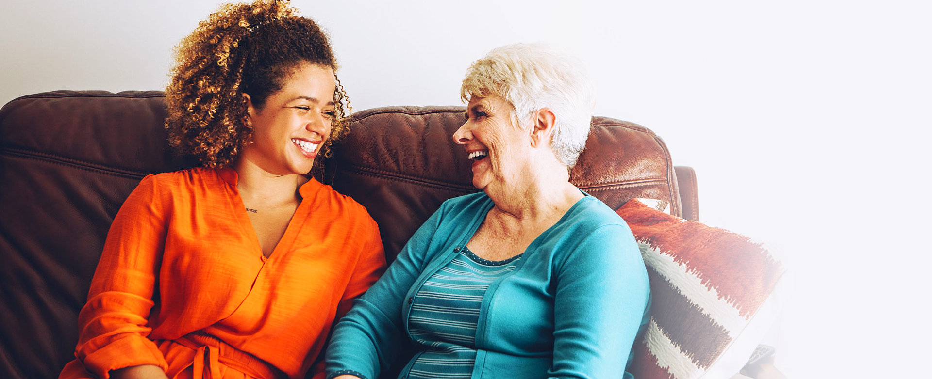 adult woman and senior woman sitting on the sofa smiling