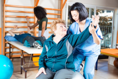 senior man and woman exercising assisting with their caregiver