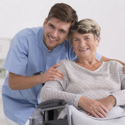 caregiver hugging senior woman sitting in the wheelchair smiling