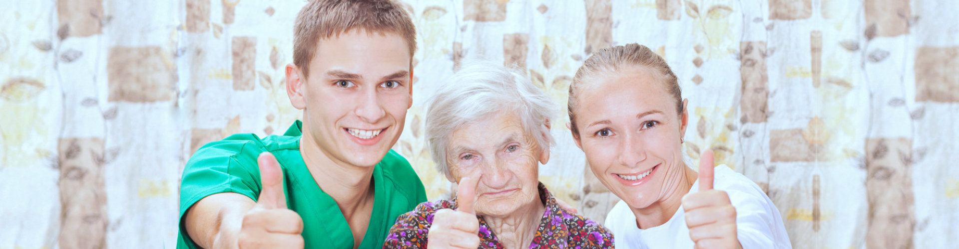 male and female caregiver with senior woman thumbs up and smiling